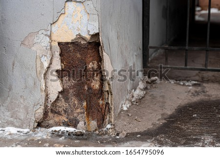 ragged corner of a building wall with old stucco and rust #1654795096