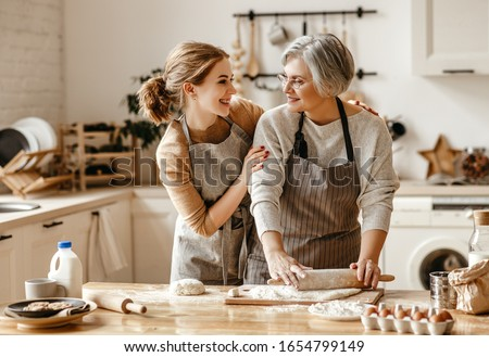 happy family grandmother  old mother mother-in-law and daughter-in-law daughter cook in kitchen, knead dough and bake cookies #1654799149