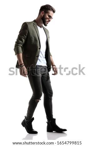 Thoughtful model wearing sunglasses, stepping on white studio background #1654799815