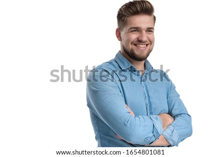 Cheerful casual man smiling and holding his hands folded at his chest, standing on white studio background #1654801081