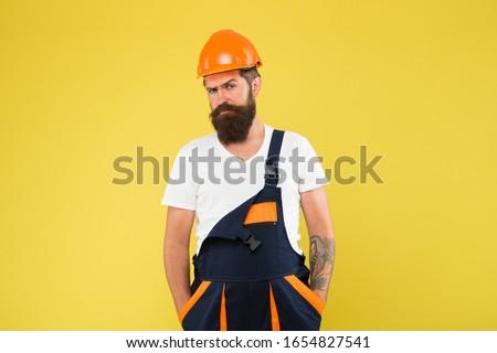 Brutal man builder. Engineer builder in uniform. Man builder hard hat. Renovating home opportunity to refresh expand and renew. Craftsman keep head safe in helmet. Building improvement and renovation. #1654827541