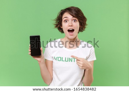 Excited woman in volunteer t-shirt isolated on pastel green background. Voluntary free work assistance help charity grace teamwork concept. Point index finger on mobile phone with blank empty screen