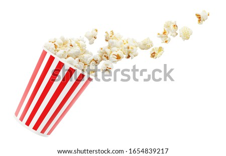 Delicious popcorn falling out of red striped paper cup, isolated on white background #1654839217