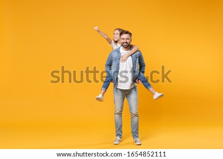 Smiling bearded man with child baby girl. Father little kid daughter isolated on yellow background. Love family parenthood childhood concept. Give piggyback ride to joyful sit on back clenching fist #1654852111