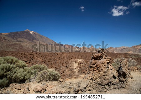 typical rough and barren volcanic crater landscape of lava fields in different colored stone and macadam in the El Teide National Park #1654852711