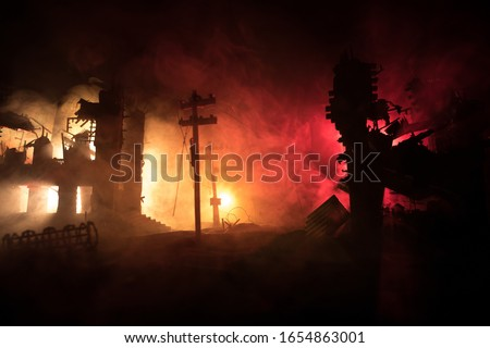 Empty street of burnt up city, flames on the ground and blasts with smoke in the distance. Apocalyptic view of city downtown as disaster film poster concept. Night scene. City destroyed by war. Royalty-Free Stock Photo #1654863001