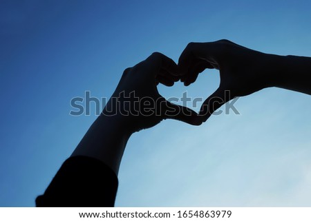 Copy space of hands making heart silhouette picture. Background with twilight sky, concept freedom and hope, Feel good and travel adventure. Holiday and traveler.