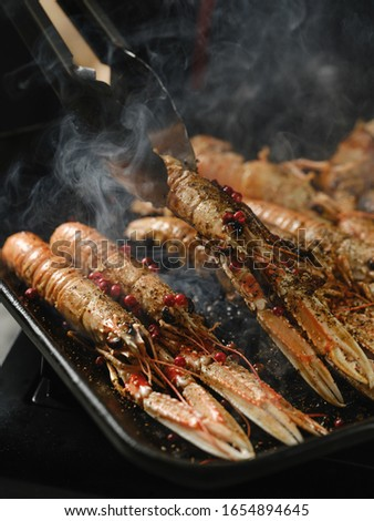 Chef cooking delicious seafood shrimps langoustine on grill pan by chef hands on black background. #1654894645
