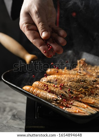 Chef cooking delicious seafood shrimps langoustine on grill pan by chef hands on black background. #1654894648