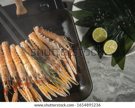 Cooking seafood shrimps and langoustine on hot grill pan by chef hands on black background. Hotel and restaurant delicious luxury dish #1654895236