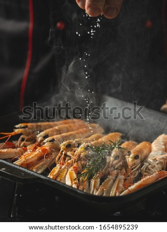 Cooking seafood shrimps and langoustine on hot grill pan by chef hands on black background. Hotel and restaurant delicious luxury dish #1654895239