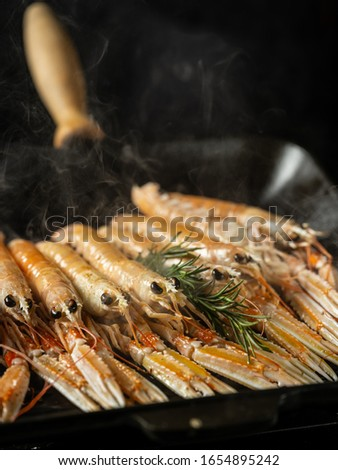 Cooking seafood shrimps and langoustine on hot grill pan by chef hands on black background. Hotel and restaurant delicious luxury dish #1654895242