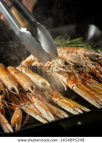 Cooking seafood shrimps and langoustine on hot grill pan by chef hands on black background. Hotel and restaurant delicious luxury dish #1654895248