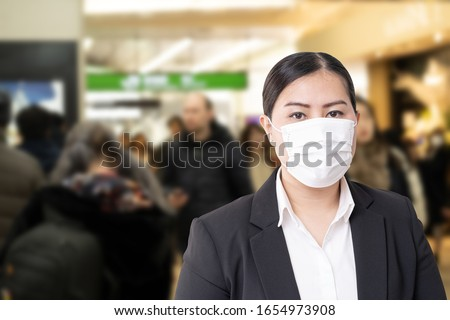 Asian woman wearing surgical mask to prevent flu disease Corona virus with blurred image of crowded #1654973908