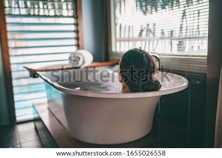 Bath taking woman relaxing in bathtub of hotel room at luxury overwater bungalow resort in Bora Bora, Tahiti. #1655026558