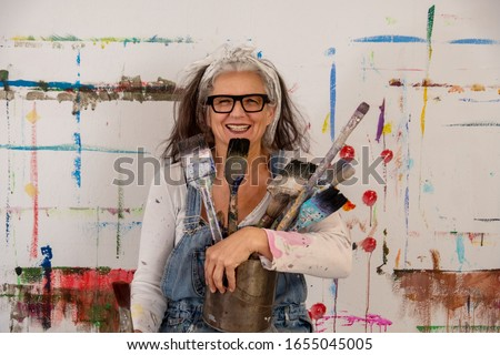 smiling older woman, proud artist, in her fifties with grey hair and black glasses and many paintbrushes Royalty-Free Stock Photo #1655045005