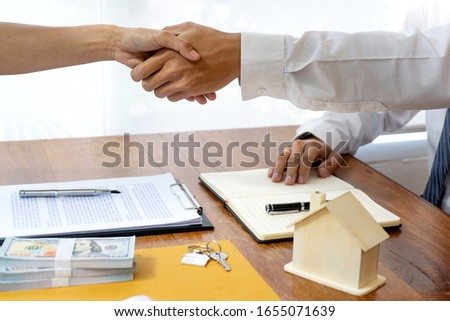 Business talk, Real estate broker agent and customer shaking hands after signing contract documents for realty purchase #1655071639