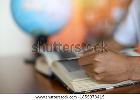 Blurred background of education or learning concept with the selective focused on the left hand of student and the blurred image of a globe ball or world map behind/ education or academic concept pic