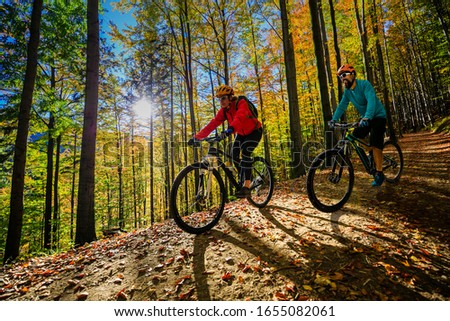 Cycling woman and men riding on bikes at sunset mountains forest landscape. Couple cycling MTB enduro flow trail track. Outdoor sport activity. #1655082061