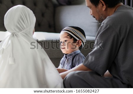 Image of Asian Muslim family in traditional costume.Muslim father with kids in their house after pray to God.Concept of Muslim people in Ramadan holy month. Royalty-Free Stock Photo #1655082427