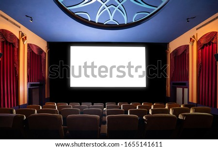 Cinema theater screen in front of seat rows in movie theater showing white screen projected from cinematograph. The cinema theater is decorated in classical style for luxury feeling of movie watching. #1655141611