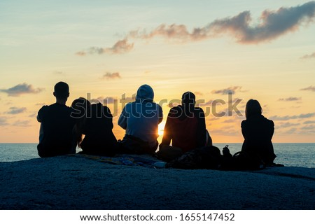 A group of young guys and girls meets dawn on a rock by the sea