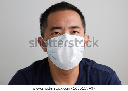 Portrait of young Asian man wearing a face mask on grey background. Health care and medical concept. #1655159437
