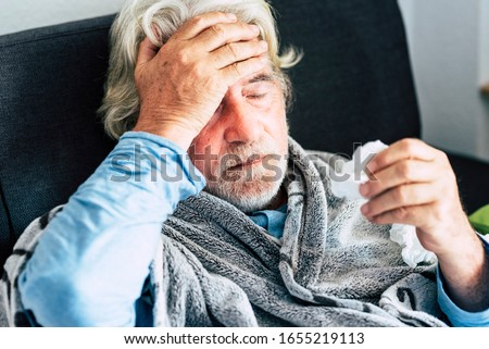 New coronavirus CoVid-19 outbreak situation with pandemic epidemic warning - adult caucasian senior old man with fever symptoms like illness cold seasonal influenza - people and virus concept Royalty-Free Stock Photo #1655219113