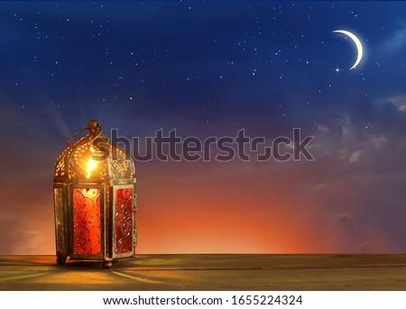Islamic greeting Eid Mubarak cards for Muslim Holidays.Eid-Ul-Adha festival celebration.Arabic Ramadan Lantern on wooden table.Decoration lamp. Crescent moon and the stars.