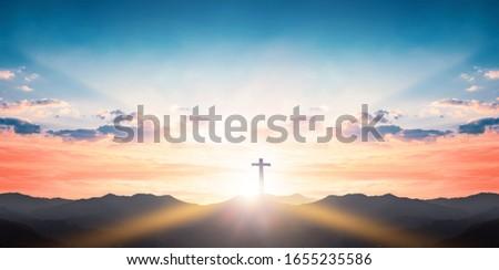 Silhouette cross on mountain sunset background