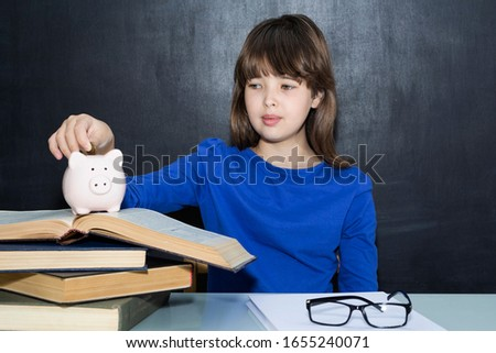 Teen puts coins in the piggy bank. The concept of paid education #1655240071