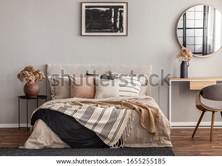 Abstract black oil painting in frame on empty beige wall of cozy bedroom #1655255185