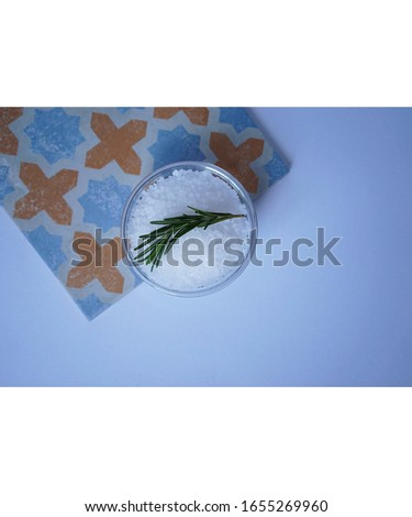 bowl with sea salt and a sprig of rosemary on a colored tiles on a neutral background in a Mediterranean style. Copy space #1655269960