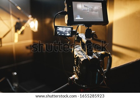 Video production backstage. Behind the scenes of creating video content, a professional team of cameramen with a director filming commercial ads. Video content creation, video creation industry. Low Royalty-Free Stock Photo #1655285923