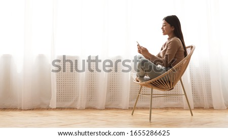 Weekend leisure. Girl using smartphone, sitting in wicker chair against window, panorama with free space #1655286625