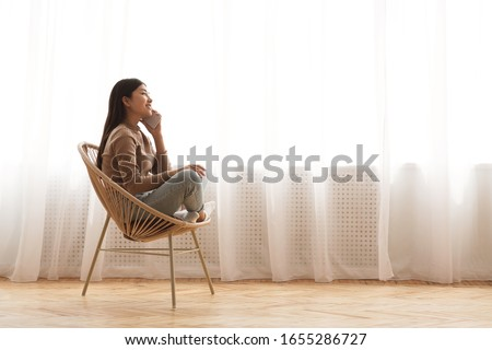 Enjoying home comfort. Girl talking on phone in cozy chair against window, side view with copy space #1655286727