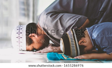 Religious Asian Muslim Man teaching his little son to pray to God in Sujud. The position involves having the forehead, nose, both hands, knees,all toes touch to ground.to praise and glorify Allah. Royalty-Free Stock Photo #1655286976
