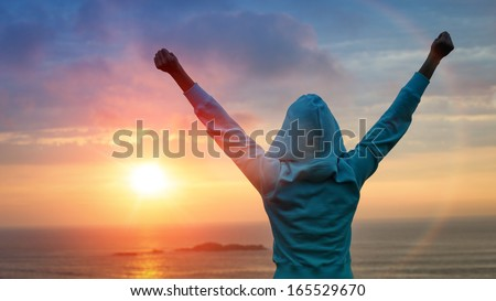 Sport and life achievements and success concept. Rear view sporty girl raising arms towards beautiful glowing sunshine. Royalty-Free Stock Photo #165529670