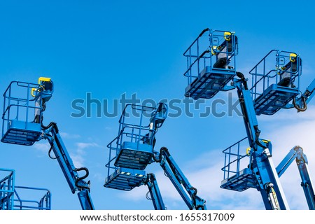 Articulated boom lift. Aerial platform lift. Telescopic boom lift against blue sky. Mobile construction crane for rent and sale. Maintenance and repair hydraulic boom lift service. Crane dealership.  #1655317009