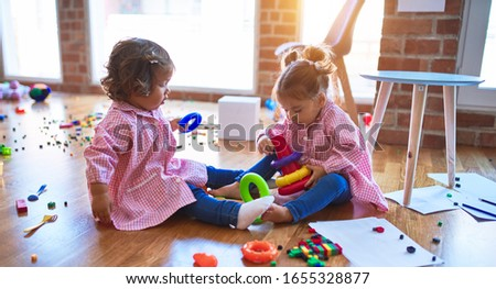 Adorable toddlers wearing uniform sitting on the floor building pyramid using hoops at kindergarten #1655328877