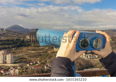 Female hands hold sightseeing touristic telescope. View from the observation deck (viewing platform) at the mountains landscape. Tourist walk, excursion. Copy space for text. #1655365210
