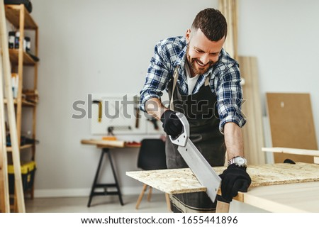 young male carpenter working in a workshop #1655441896