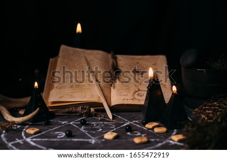 Open old book with magic spells, runes, black candles on witch table. Occult, esoteric, divination, superntural and wicca concept. Halloween vintage background Royalty-Free Stock Photo #1655472919