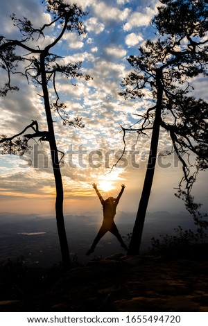 the man stand between two tree and he is jump with sunrise backg #1655494720