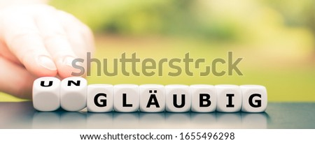 """Hand turns dice and changes the German word """"gläubig"""" (religious) to """"ungläubig"""" (irreligious). #1655496298"""