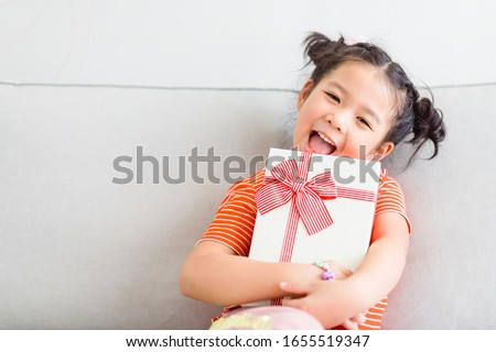Little asian girl smile and excited and holding red gift box on sofa   in living room background.child holding gift box in Christmas and New year concept. #1655519347