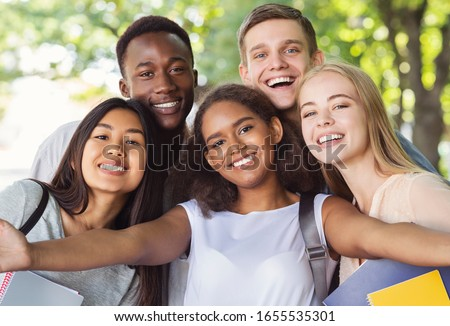 Cheerful international friends teenagers taking selfie while walking in summer park, happy memories concept Royalty-Free Stock Photo #1655535301