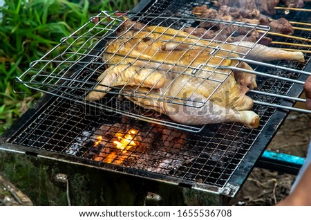 Barbecued fresh whole chicken outdoors in the forest #1655536708