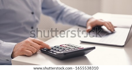 Savings, Finances And Economy Concept. Mature man with counting money using calculator and laptop computer #1655538310