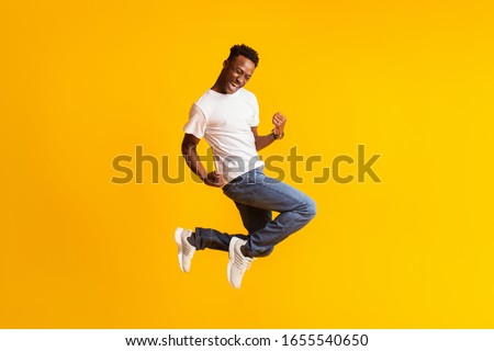 Successful moment. Happy excited young black man jumping over yellow background, copy space